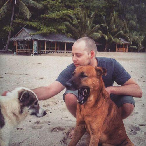 Andre von soulvideo mit Hunden am Strand statt mit Kamera beim Drehen eines Hochzeitsvideos in Salzburg